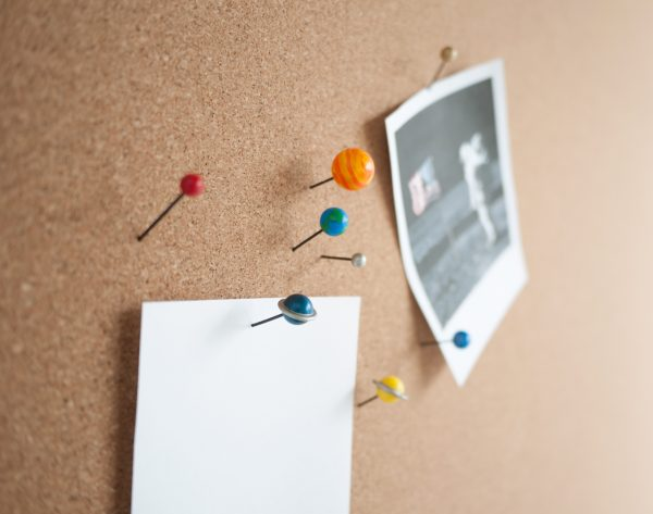 Planet Pins by Duncan Shotton, in use, holding photos and paper memos to a cork board